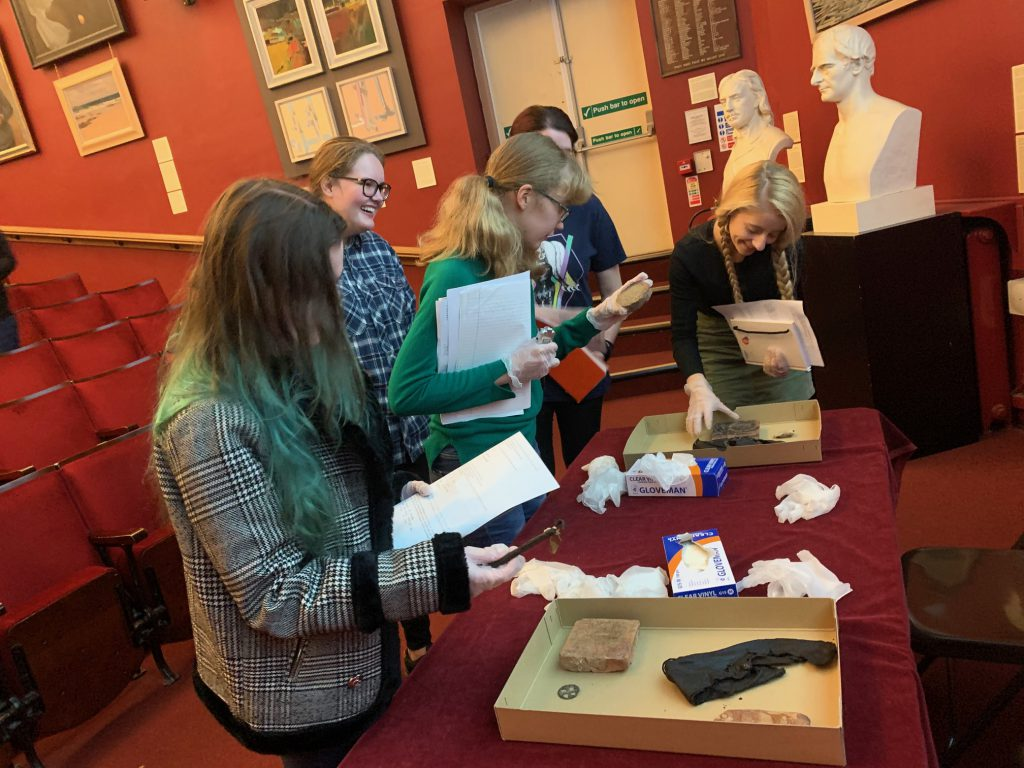 Students with everyday historical objects at the Grosvenor Museum in 2019 (pre-COVID).